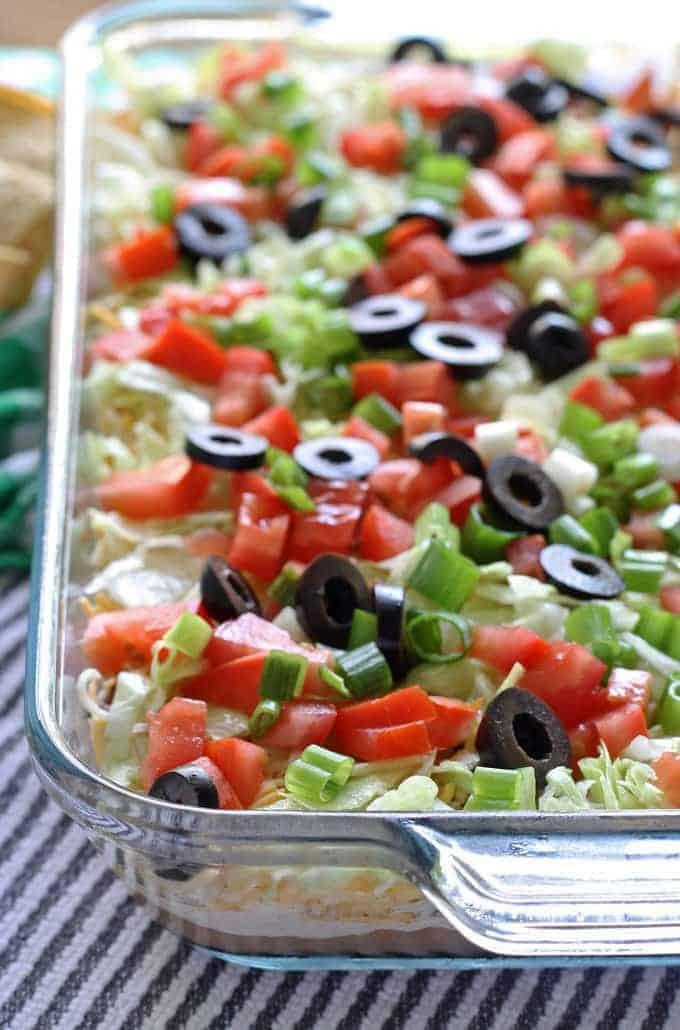 Go big with this 8 layer taco dip recipe - it is the perfect appetizer for large crowds. It's full of meat, cheese, veggies and more! | honeyandbirch.com