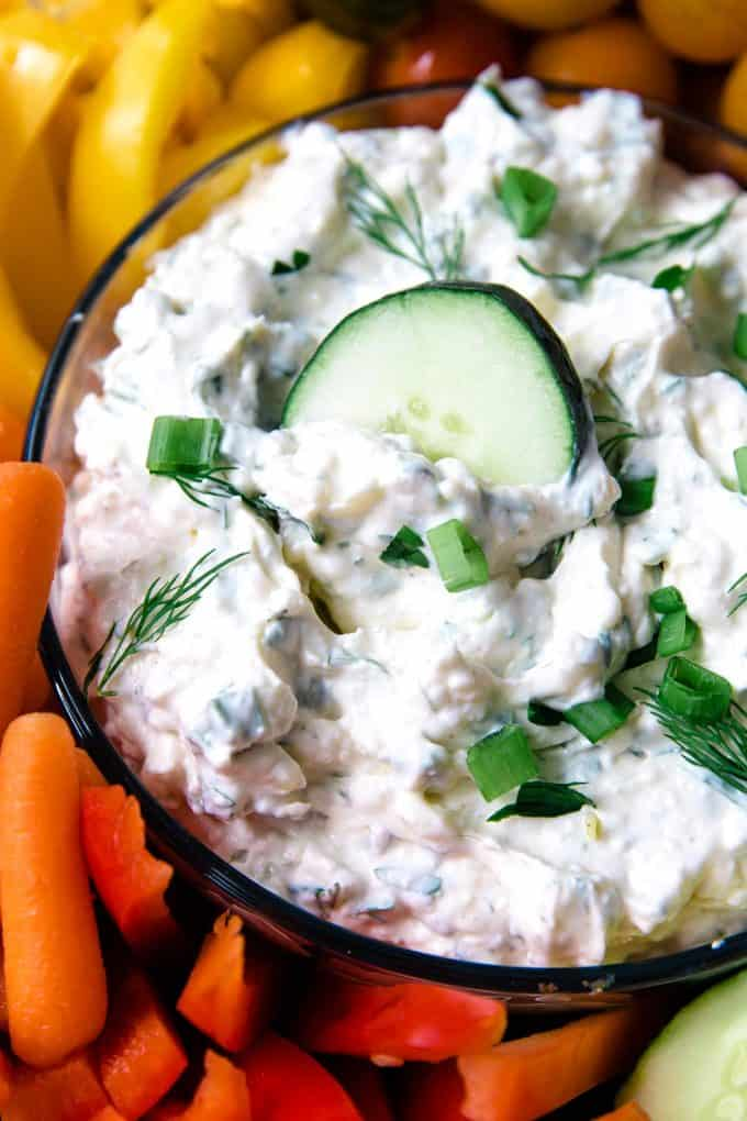 bowl of veggie dip with a cucumber slice