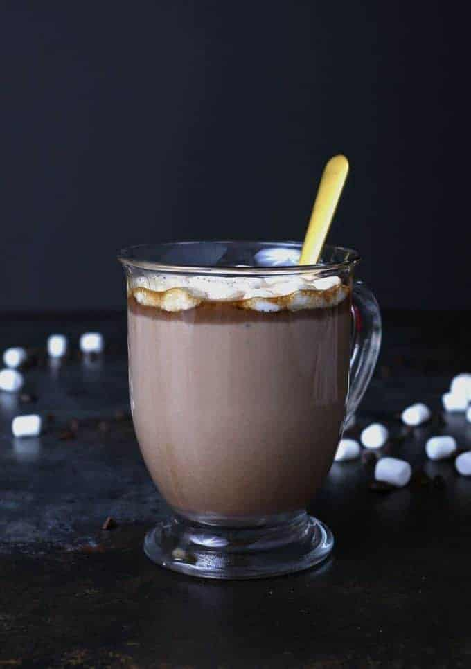 Kahlua hot cocoa in a clear mug with a gold spoon