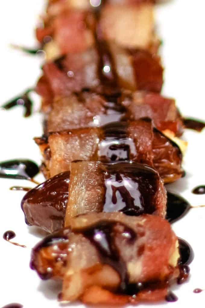 bacon wrapped dates on a white plate