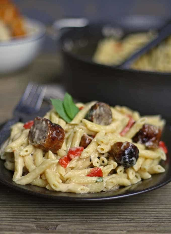This brown butter alfredo pasta with roasted red peppers and sausage is perfect for Sunday dinner and a great way to use up leftover grilled sausage. | honeyandbirch.com