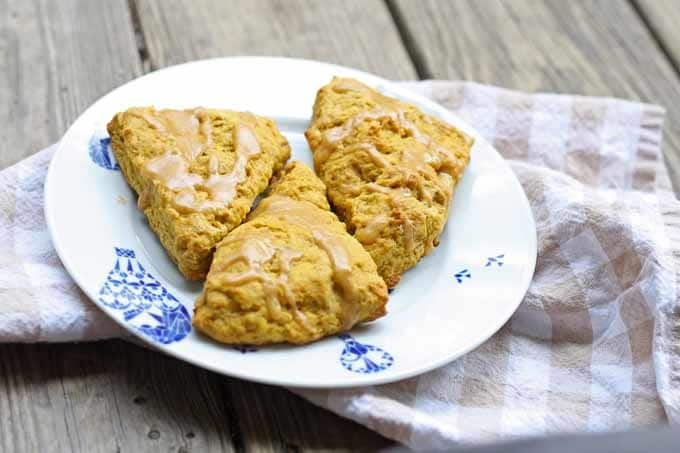 Pumpkin spice scones on a plate with a tan towel