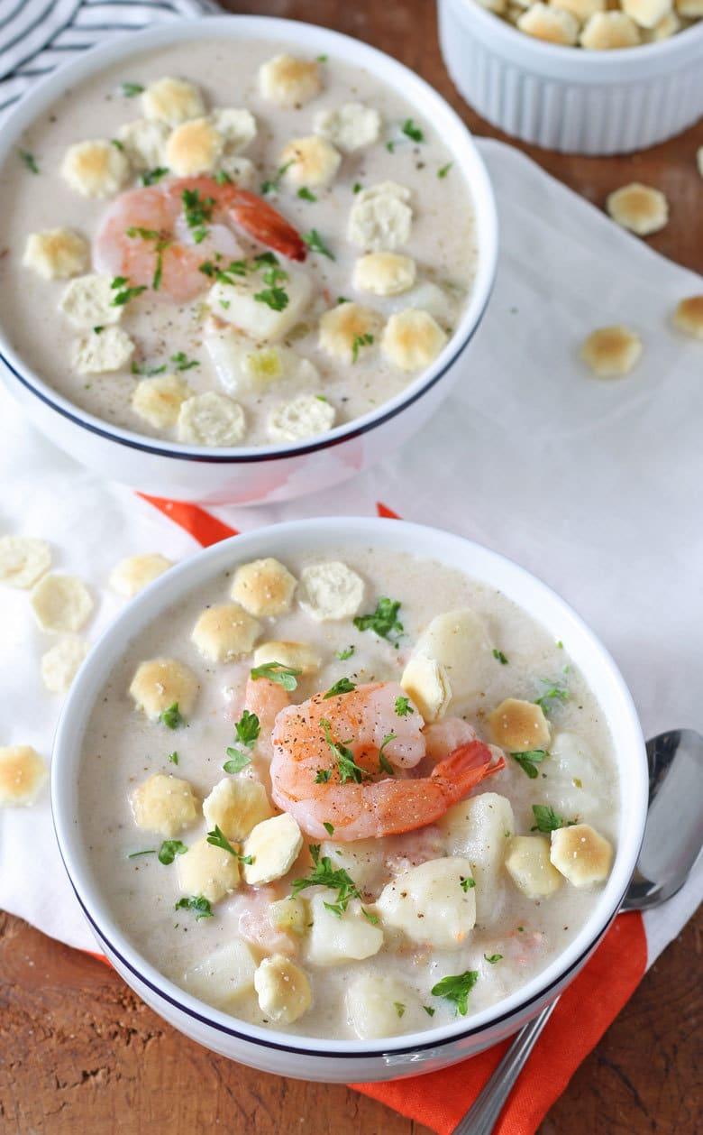 two white bowls full of potato shrimp chowder