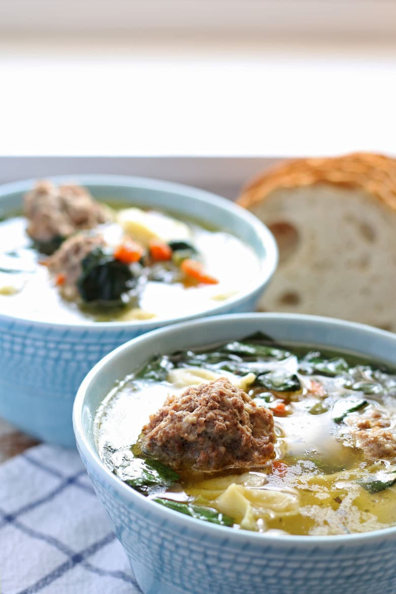 two blue bowls of soup with large meatballs