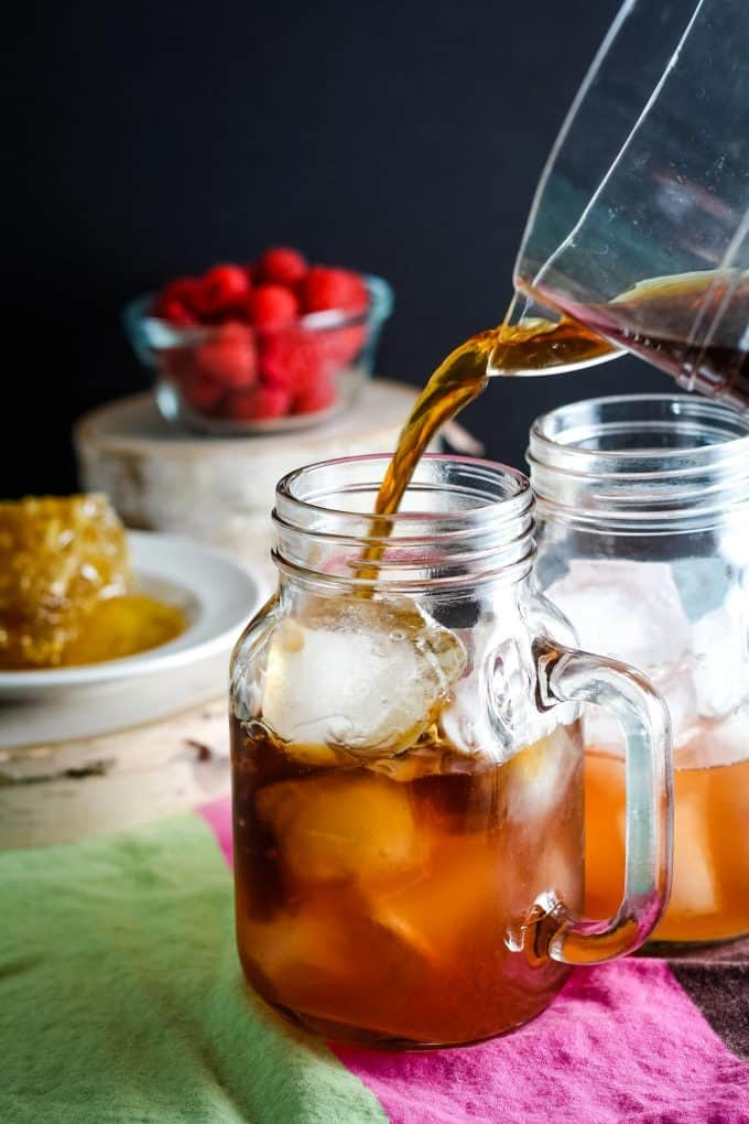 adding ice tea to mason jar mug