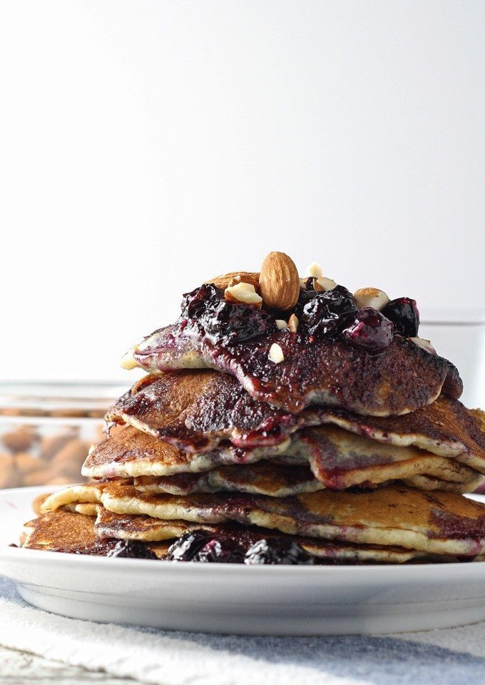 Start your day with these delicious blueberry almond pancakes, topped with homemade honey poached blueberries. Perfect for breakfast! | honeyandbirch.com