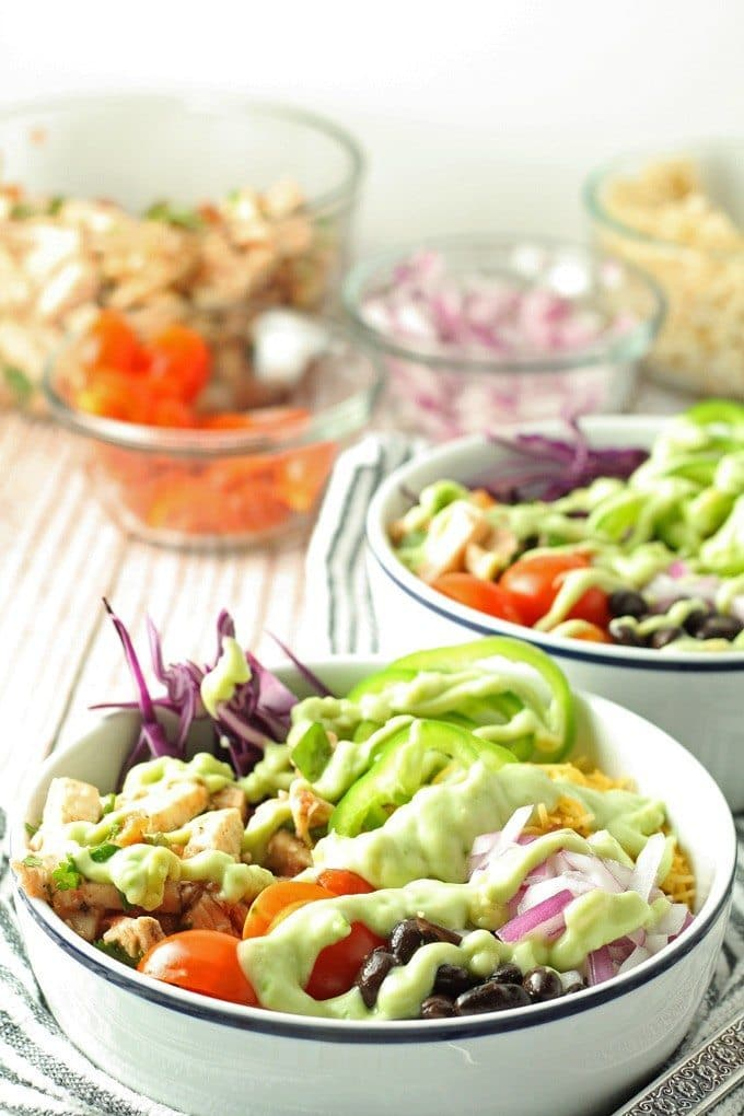 Leftover chicken burrito bowls topped with avocado crema. Full of veggies and flavor, they are the perfect use for leftover chicken! | honeyandbirch.com