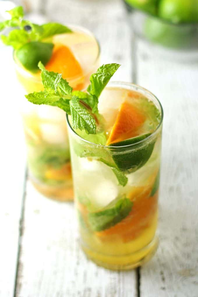 two orange mojitos on white wood