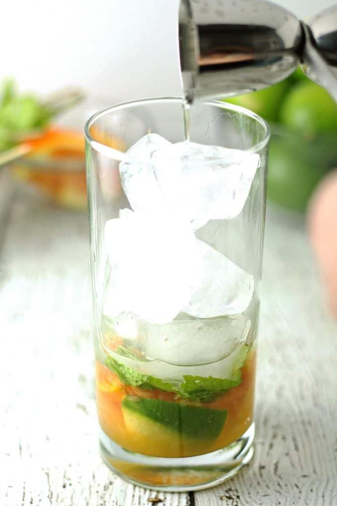 adding rum to a mojito