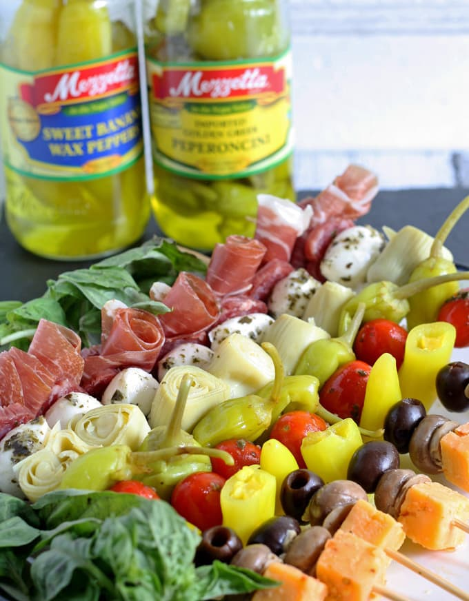 Plate of antipasto skewers with pepper jars.