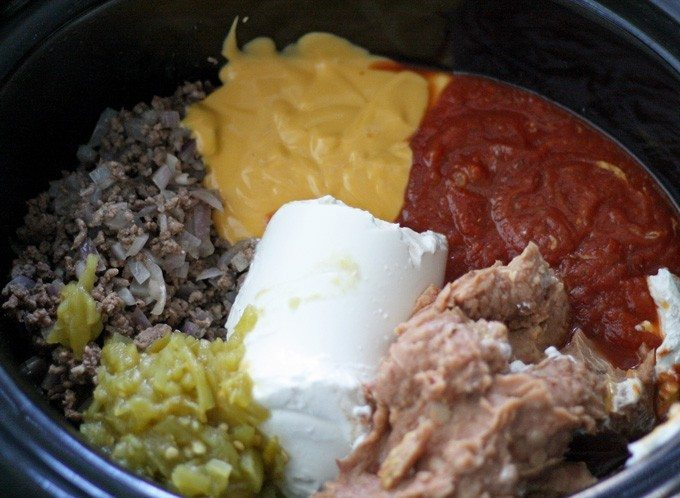 This slow cooker taco dip is perfect for parties - it can easily be thrown together in 2 hours with store bought ingredients! | honeyandbirch.com
