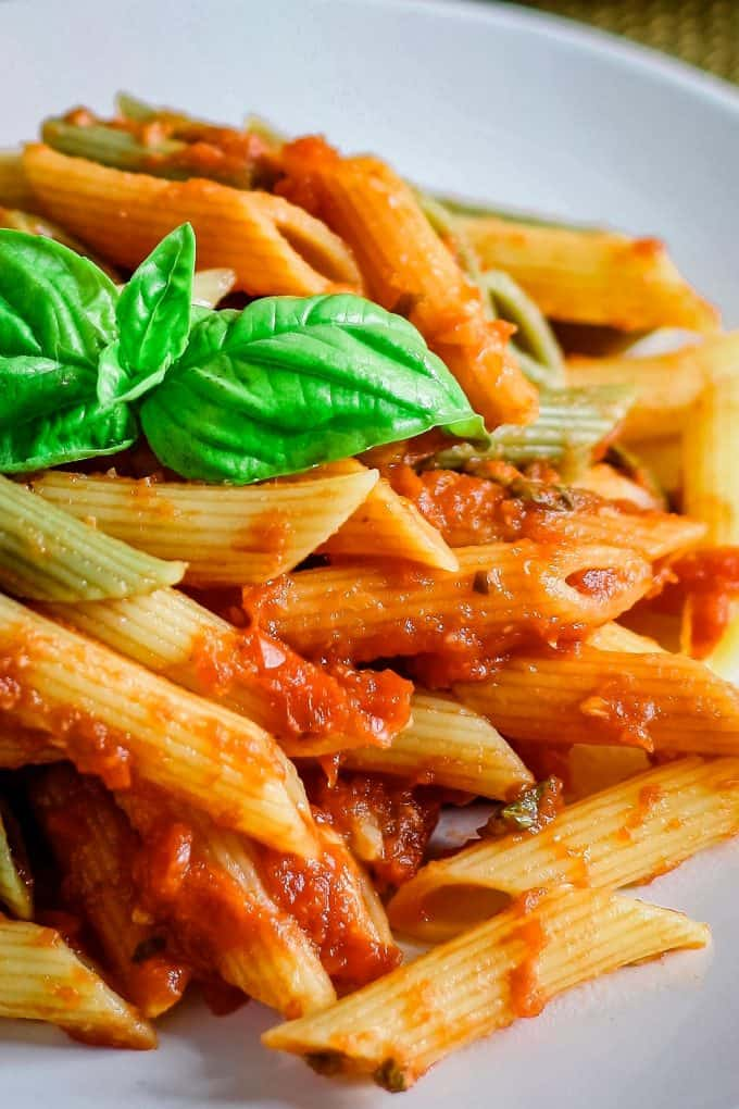 a plate of pasta tossed in basil roasted garlic tomato sauce