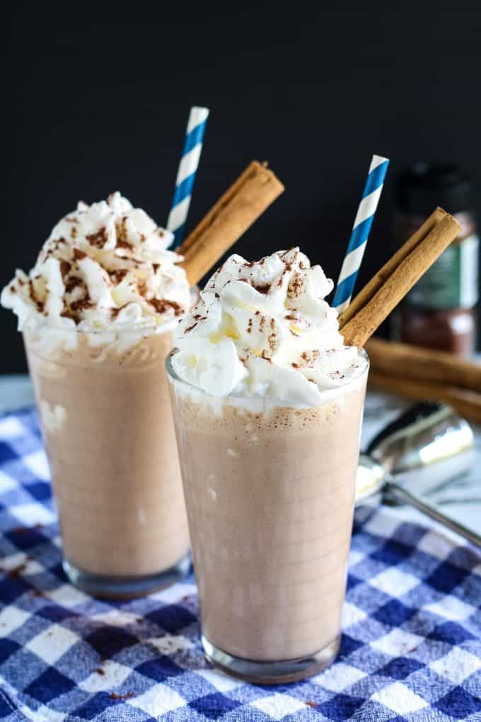 two Mexican chocolate milkshakes garnished with whipped cream and cinnamon sticks
