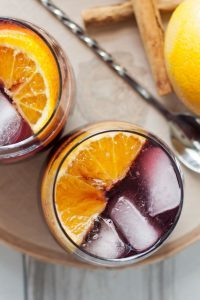 This orange red wine spritzer is a great cocktail for any season. Mix up a batch of cinnamon simple syrup, grab a bottle of your favorite red and try this drink today!