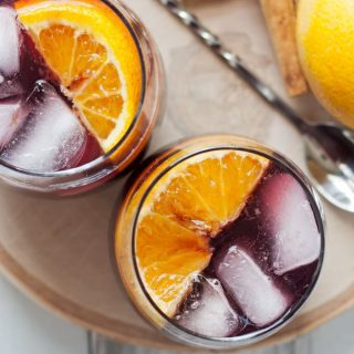 This orange red wine spritzer is a great cocktail for fall and winter. Mix up a batch of cinnamon simple syrup, grab a bottle of your favorite red and try this drink today! | honeyandbirch.com