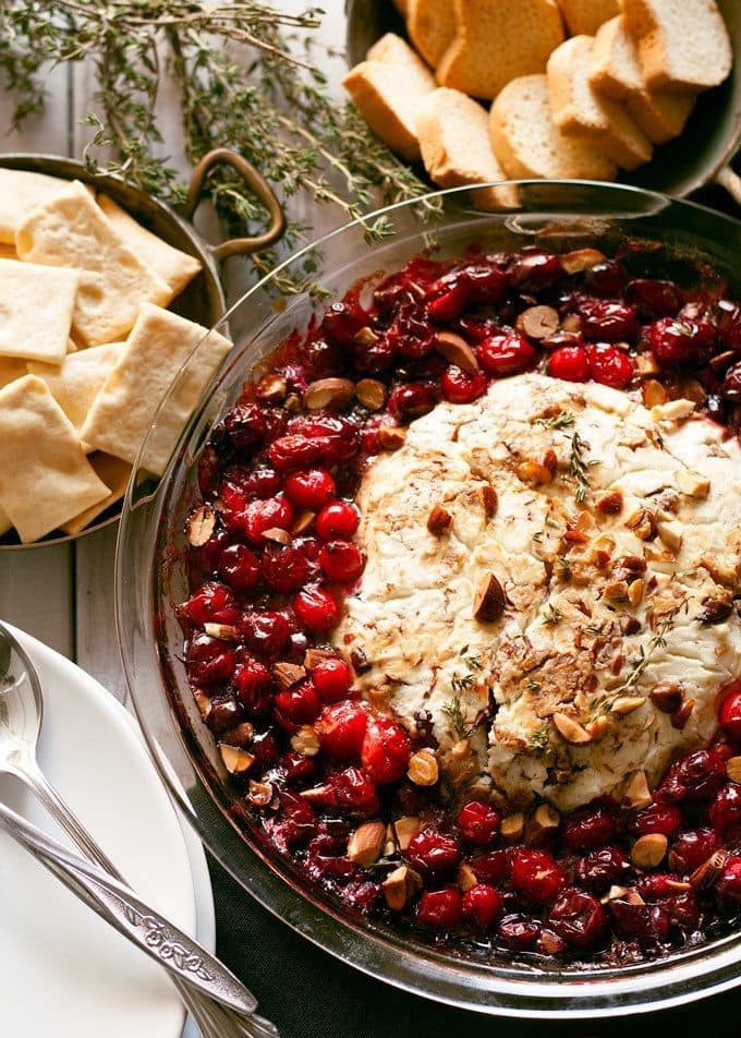 baked goat cheese roasted cranberry appetizer in a glass serving dish