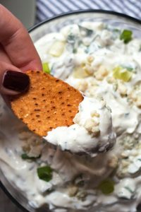 creamy blue cheese dip with a hand holding a chip