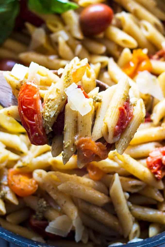 tomato and pesto pasta on a wooden spoon