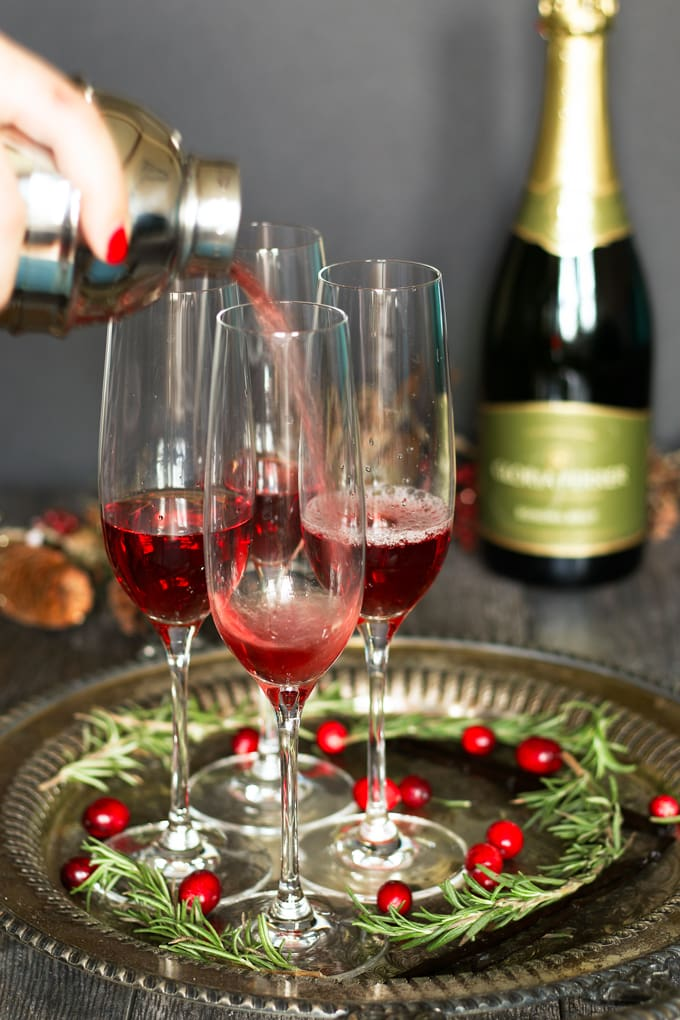 pouring cranberry juice and vanilla vodka into champagne flutes