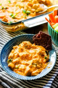 buffalo chicken dip in a blue bowl with a chip