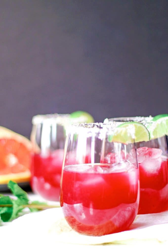 three grapefruit hibiscus margaritas grapefruit slices and fresh mint
