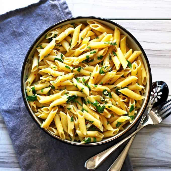 pasta aglio e olio on a marble table with a blue napkin
