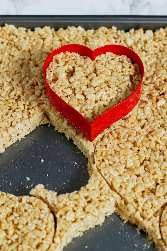 Rice Krispies on a sheet pan with a heart shaped cookie cutter