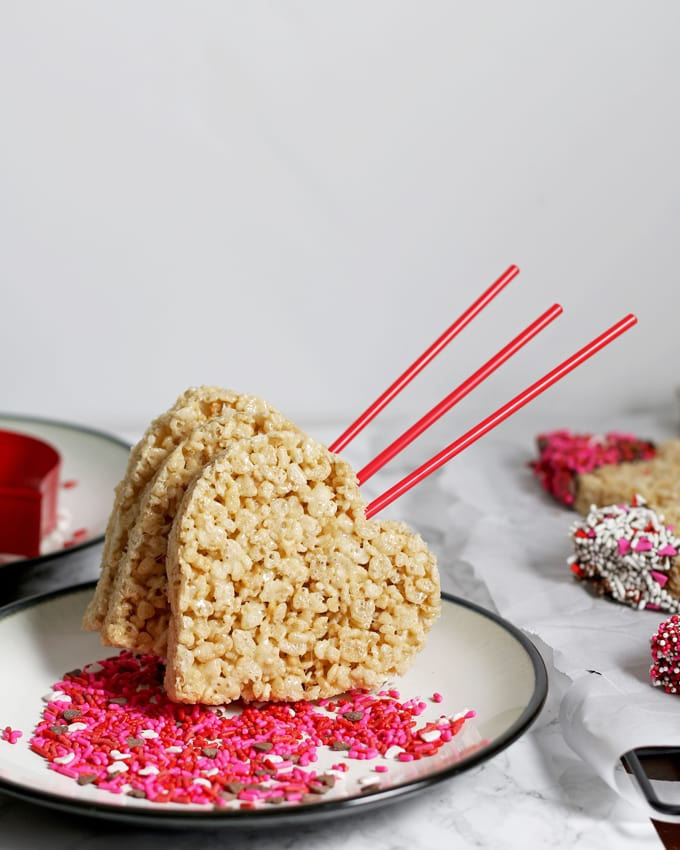 These rice krispie pops are the perfect easy Valentine's Day treat for you and your kids! Whip up a batch of rice krispie treats, dip them in chocolate and apply sprinkles! | honeyandbirch.com
