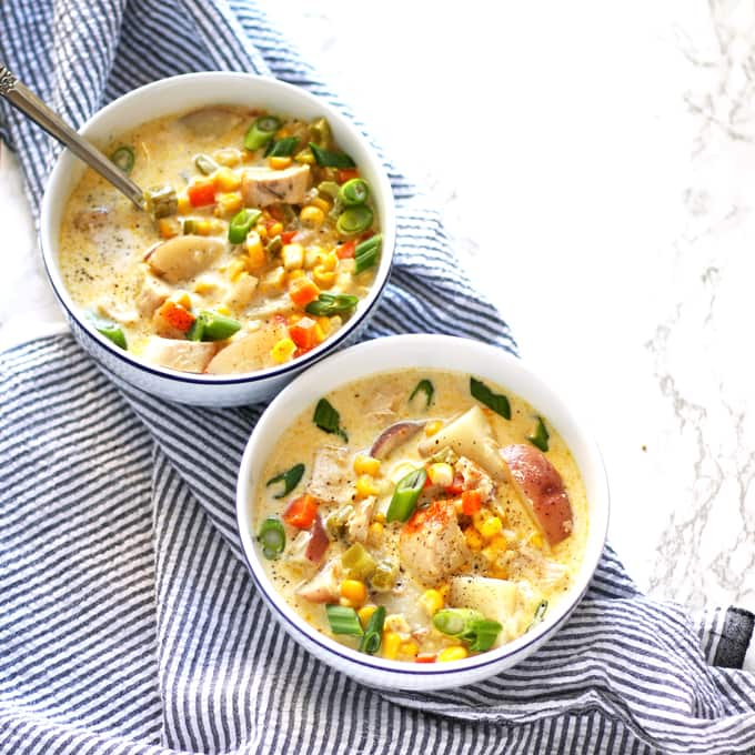 chicken corn chowder in two bowls on a napkin