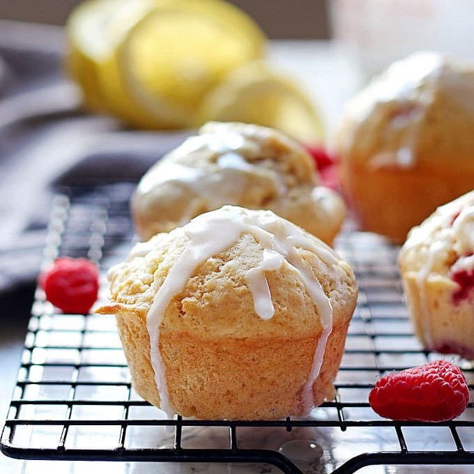 These raspberry lemon muffins with lemon glaze are sweet and tart at the same time! They are perfect for brunches, breakfast or snacks on-the-go! | honeyandbirch.com