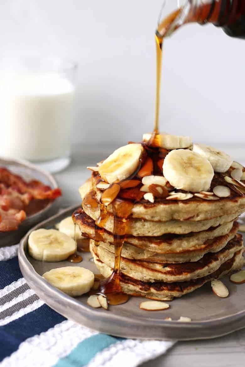 banana almond pancakes with syrup being poured on top