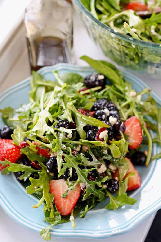 picture of berry goat cheese salad on a round blue plate