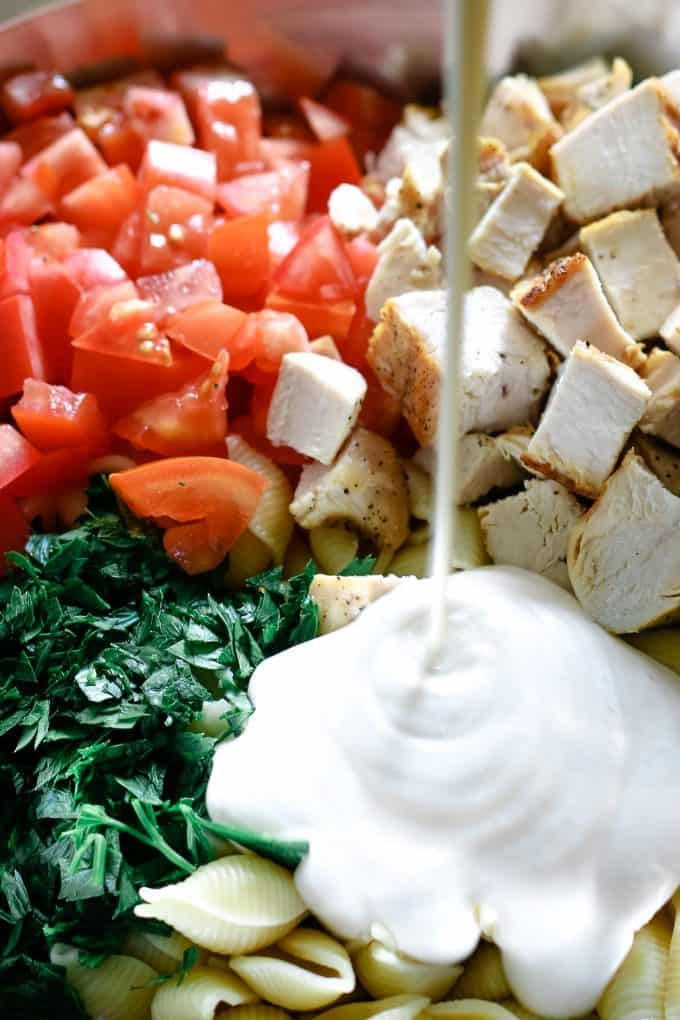 ranch being added to bowl of chicken ranch salad ingredients