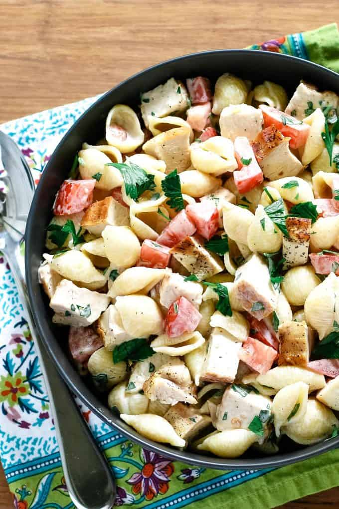 bowl of grilled chicken ranch pasta salad on a wooden board