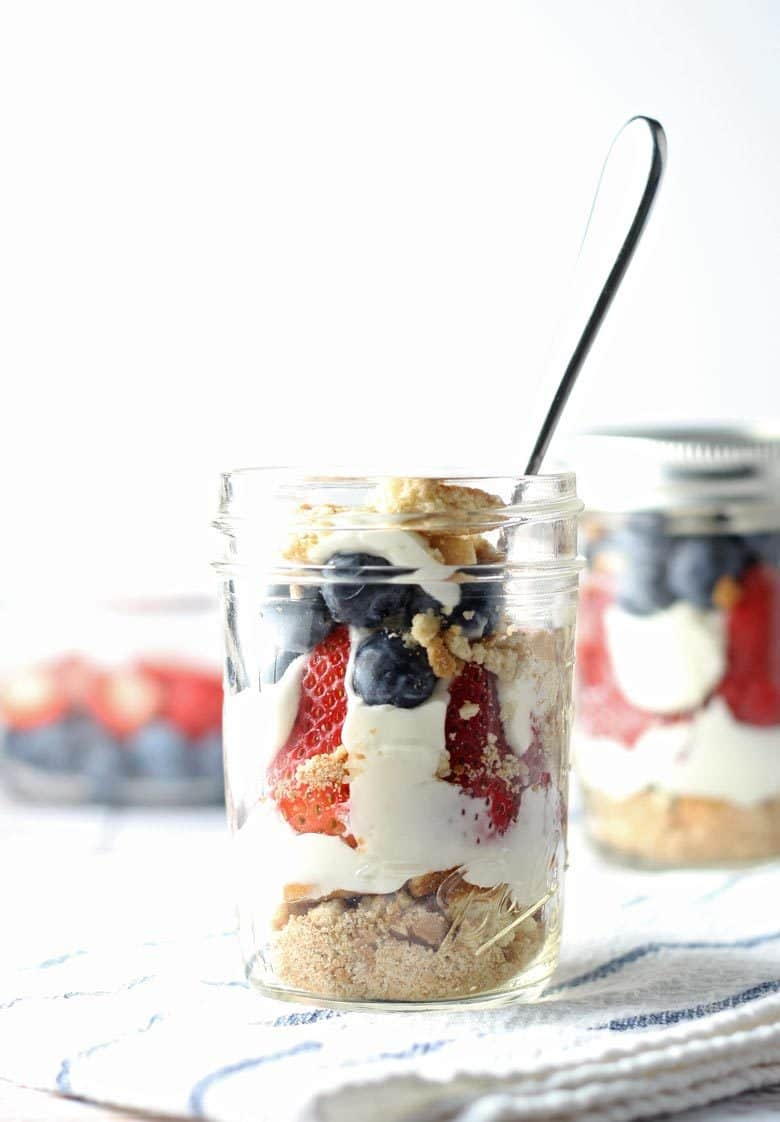 red white and blue cheesecake parfait in a mason jar