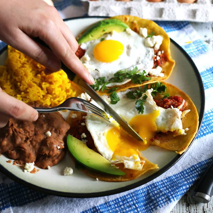 This huevos rancheros recipe is a delicious way to start your day! Made with homemade salsa and fresh eggs, it is hearty, easy to make, vegetarian, and perfect for weekend brunch or large family gatherings. Serve with a side of refried beans and rice! | honeyandbirch.com