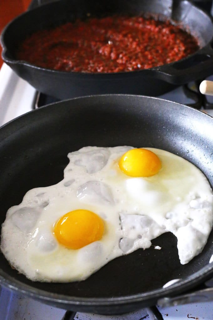 two eggs frying in a pan