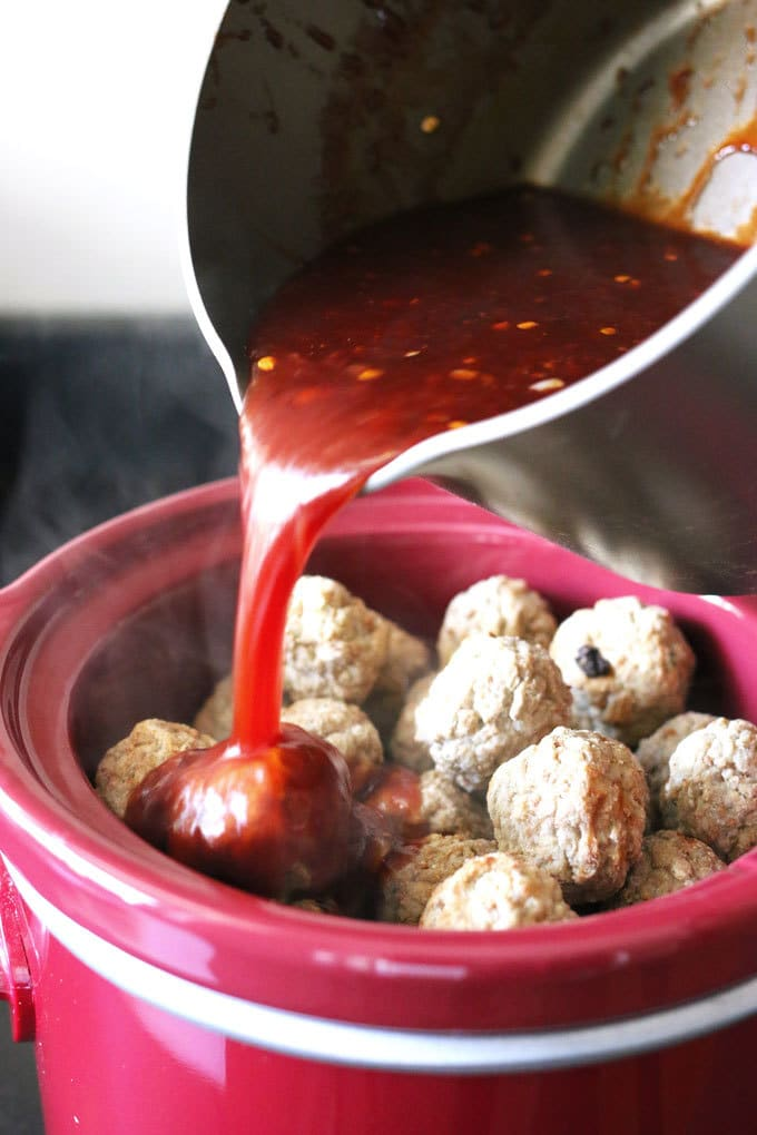 pouring sauce over meatballs