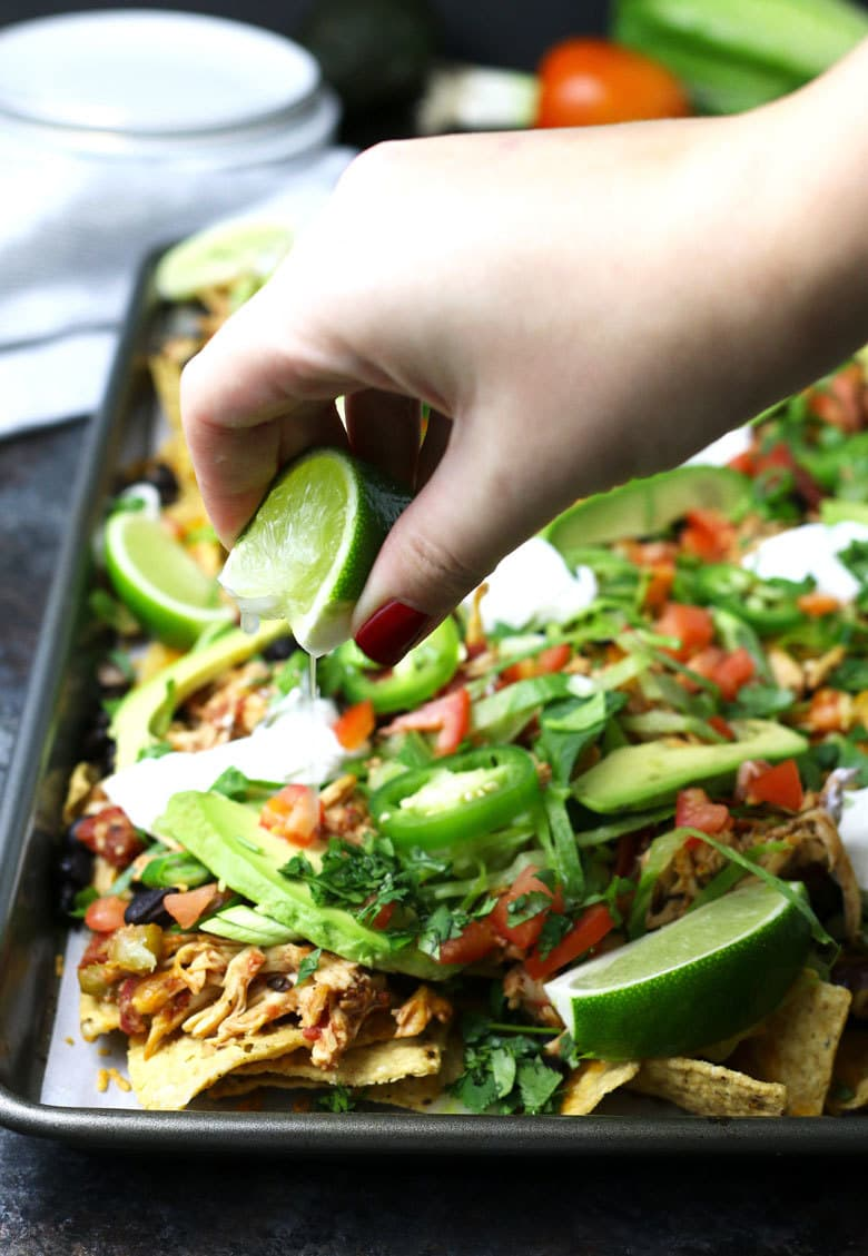 squeezing lime juice on chicken nachos