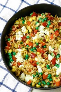 bowl of vegetable fried rice and a blue and white napkin