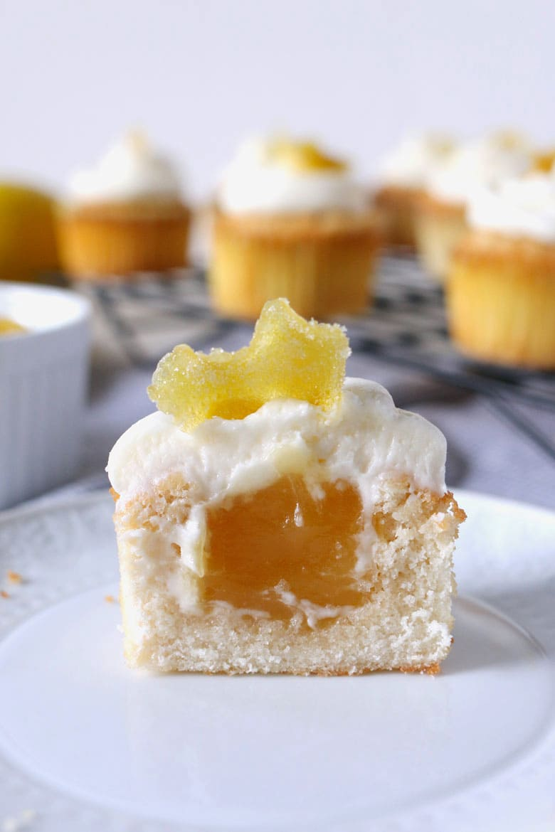 These white cupcakes with lemon frosting are filled with lemon curd and topped with candied lemon peel. They're the perfect sweet treat! This homemade cupcake recipe is easy to make and you can't go wrong with a filled cupcake topped with a fancy decoration!