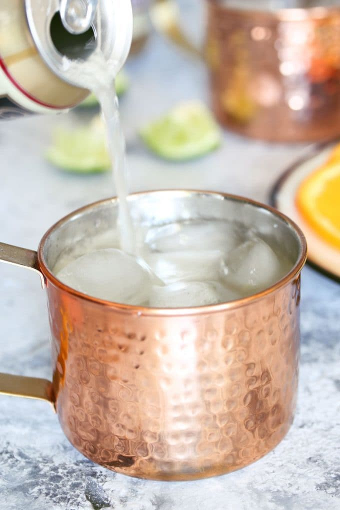 pouring ginger beer into a mule cocktail