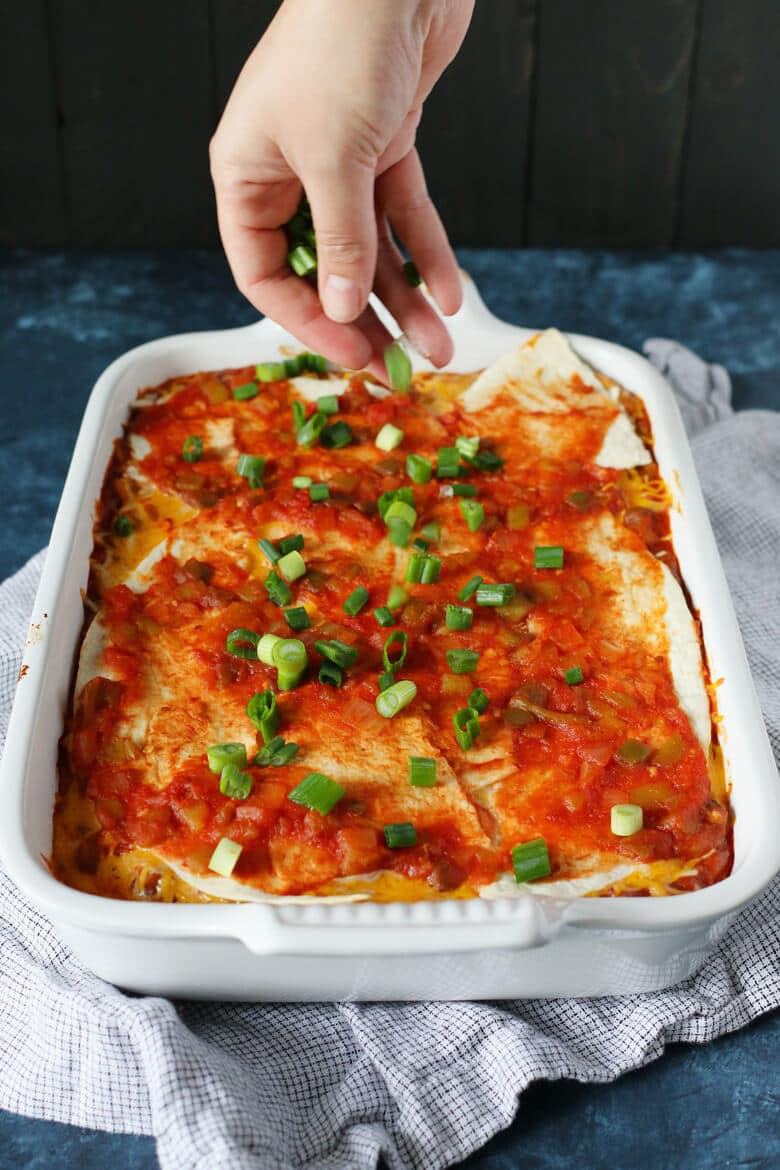 Cooked bean burrito casserole being garnished with green onions