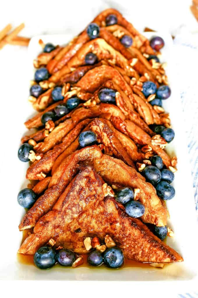 plate of cinnamon French toast topped with nuts, blueberries and syrup