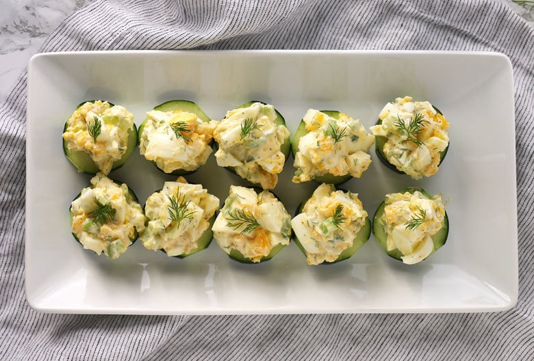 egg salad cucumber canapé on a white plate