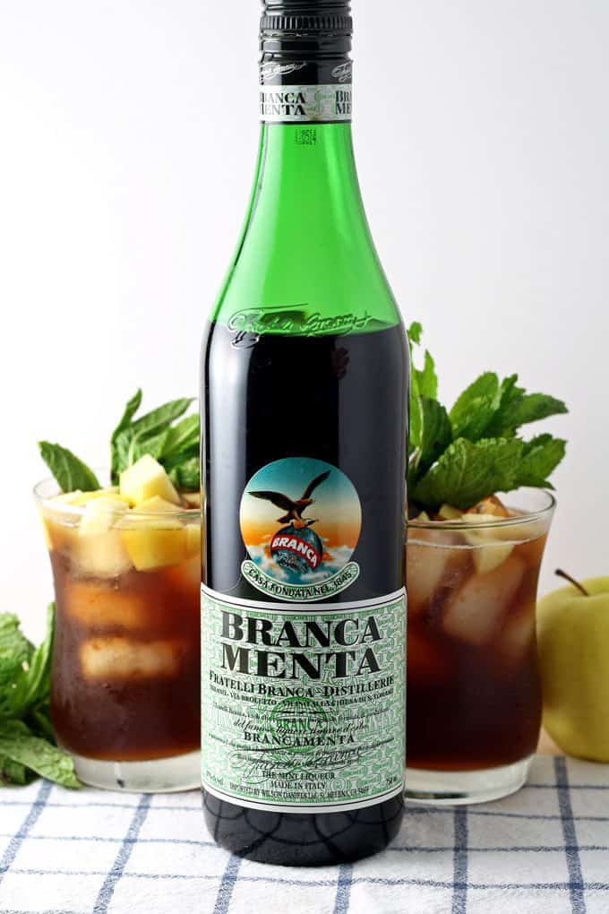 bottle of branca menta with two apple mint iced tea cocktails
