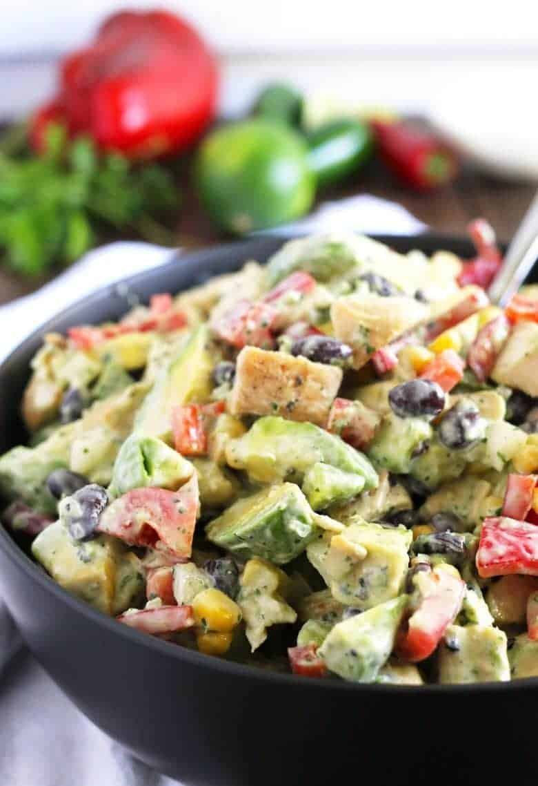 grilled chicken avocado salad in a black bowl