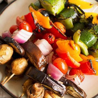 These rainbow veggie kabobs are the perfect summer side dish! Serve them with my delicious and easy to make grilled lemon garlic sauce.