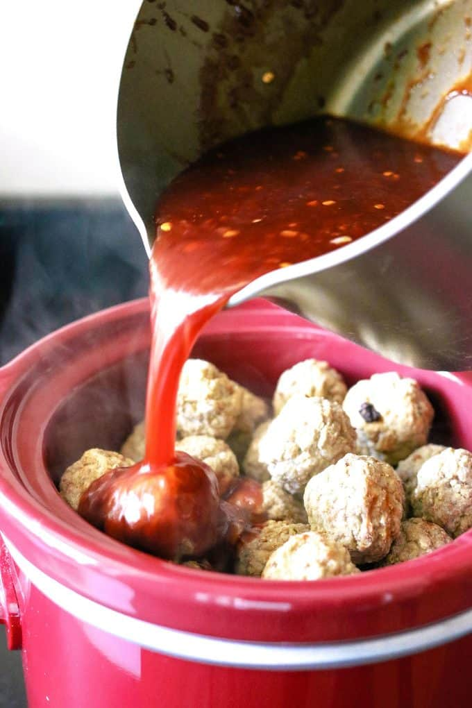 chili pepper jelly sauce being poured on top of frozen meatballs