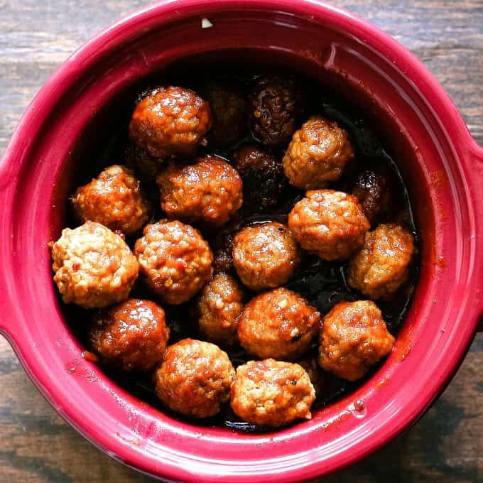 cooked sweet and spicy meatballs in a red crockpot